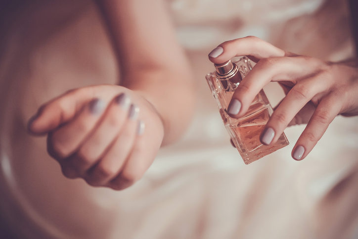 woman-applying-perfume-on-her-wrist