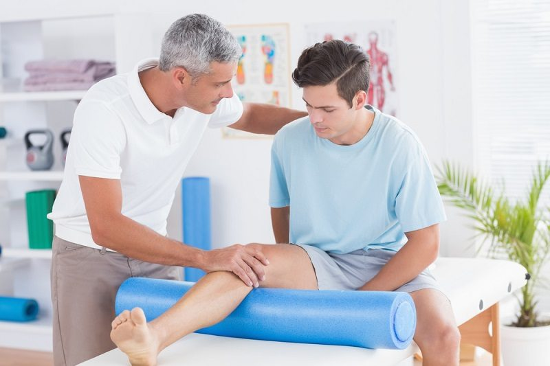 doctor-examining-his-patient-leg-in-medical-office