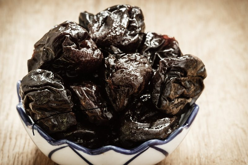 dried-plums-prunes-in-bowl-on-wooden-table