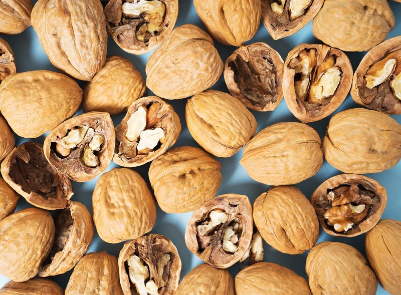 walnuts-whole-in-their-skins-chopped-on-blue-background